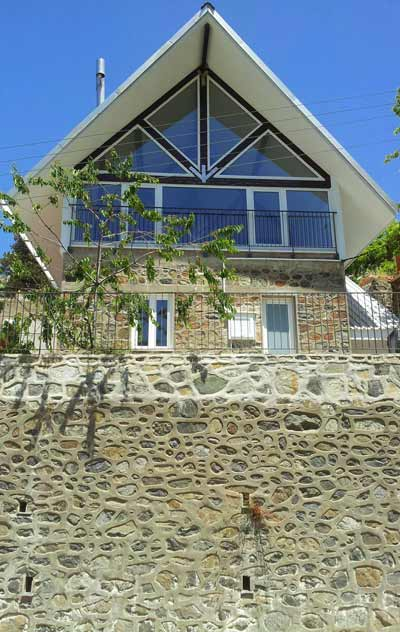 Front view of a modern chalet built above a large old stone wall