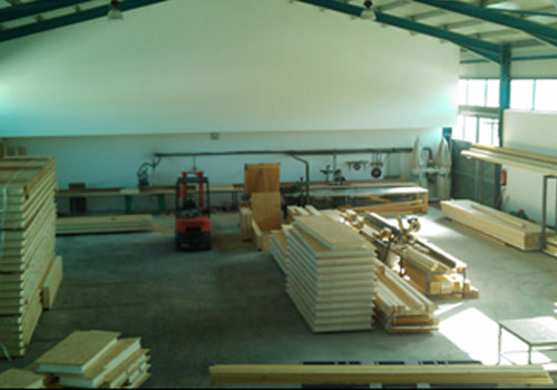 Internal view of a factory space with an orange forklift showing timber panels and planed lumber.