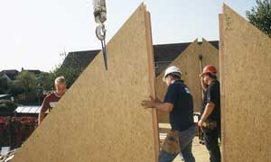 Three contractors holding a triangular timber wall panel while it is hoisted by a crane.
