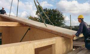 A contractor holding a timber roof panel while a crane lifts it into place.