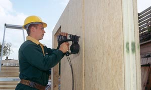 Contractor with yellow helmet with a nail gun fixing two timber wall panels together.