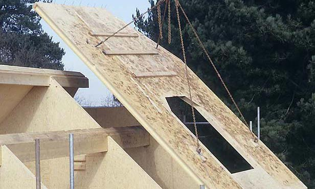 A timber roof panel is hoisted with chains with a crane onto a timber house.