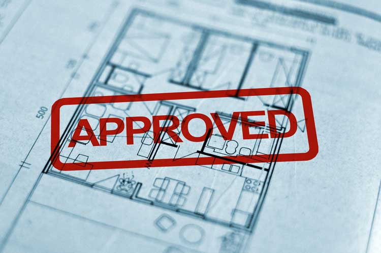A house blueprint showing a diagram with a large red stamp on it that says approved.