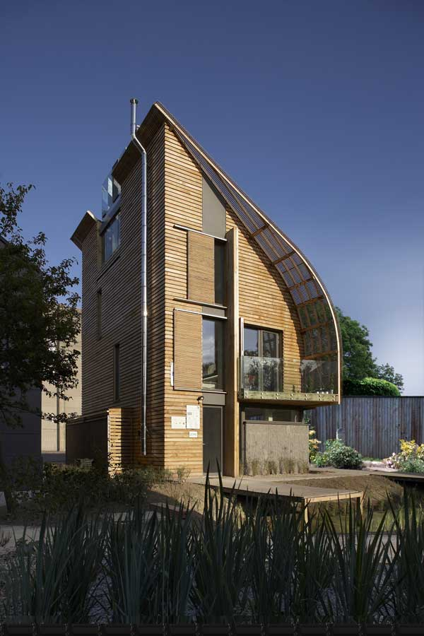 A futuristic eco house clad in timber with a curved roof and moveable sun blinds