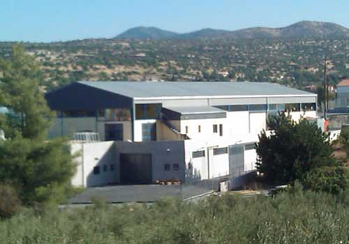 An external view of a modern factory in a green valley surrounded by trees and green hills.