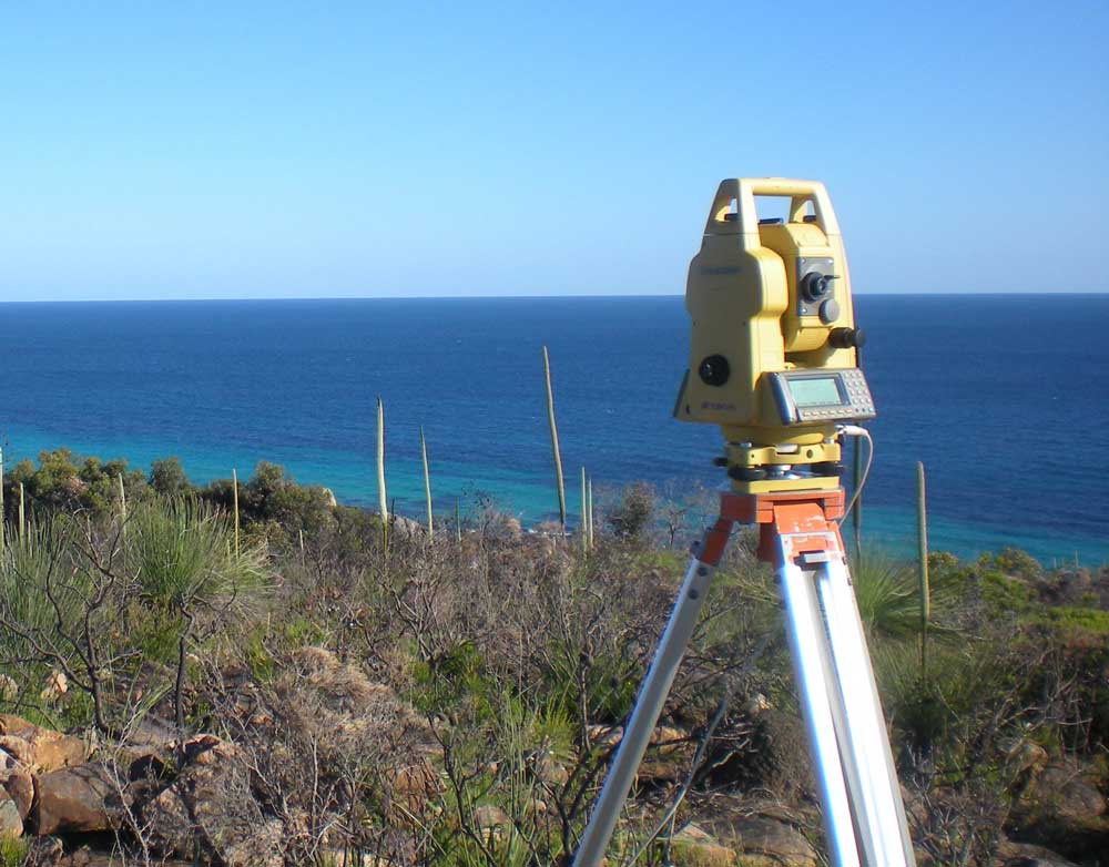 A surveyor's level positioned in a building plot adjacent to the sea and a blue sky.