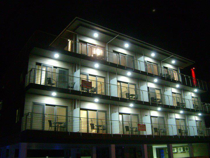 A nightime view of an Eco apartment block with a black sky and lit balconies