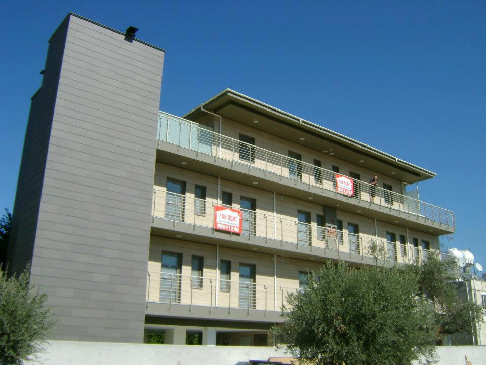 A daytime view of an Eco apartment block with trees and a clear blue sky