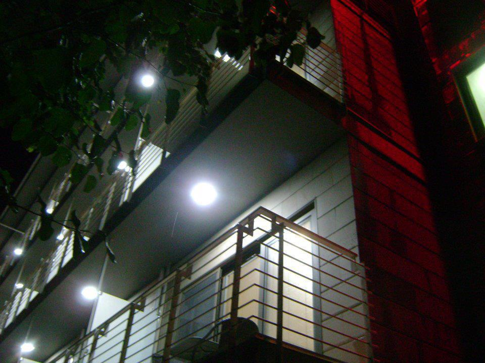 A nightime view upwards towards led lit balconies of an apartment block with red and white light.